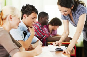 Teenage students in the classroom with teacher.